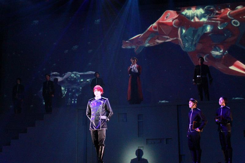 キルヒアイス(加藤将)と、後方に映像で映る赤く塗られた彼の旗艦