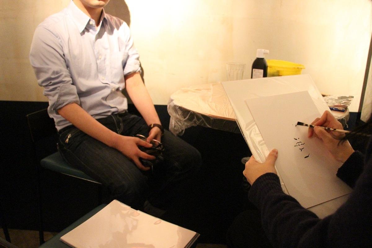 会場で行われるライブ・ポートレートの様子。岩井が割り箸を使って描いていくさまを、間近で見ることが出来る。