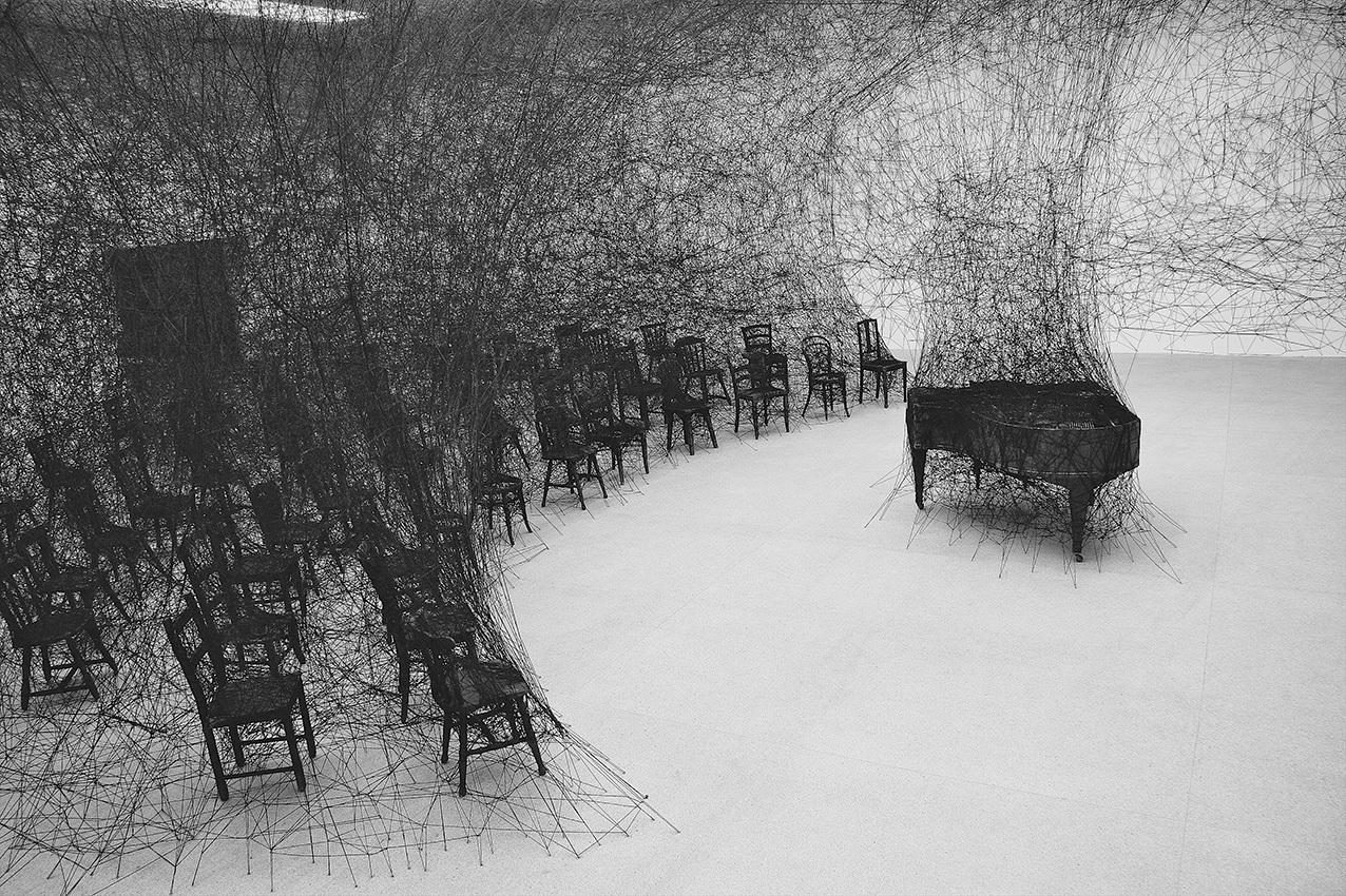 塩田千春 《静けさの中で》 2008年 焼けたピアノ、焼けた椅子、黒毛糸 展示風景:「存在様態」パスクアートセンター(ビール/ビエンヌ、スイス)2008年 撮影:Sunhi Mang