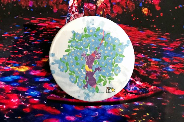 《グラフィティネイチャー》で描いた花の絵に、別スタッフの描いたトカゲを組み合わせて缶バッジに。なお、イラストのデザインはどれも素敵なので、絵に自信がなくてもまったく問題ない。