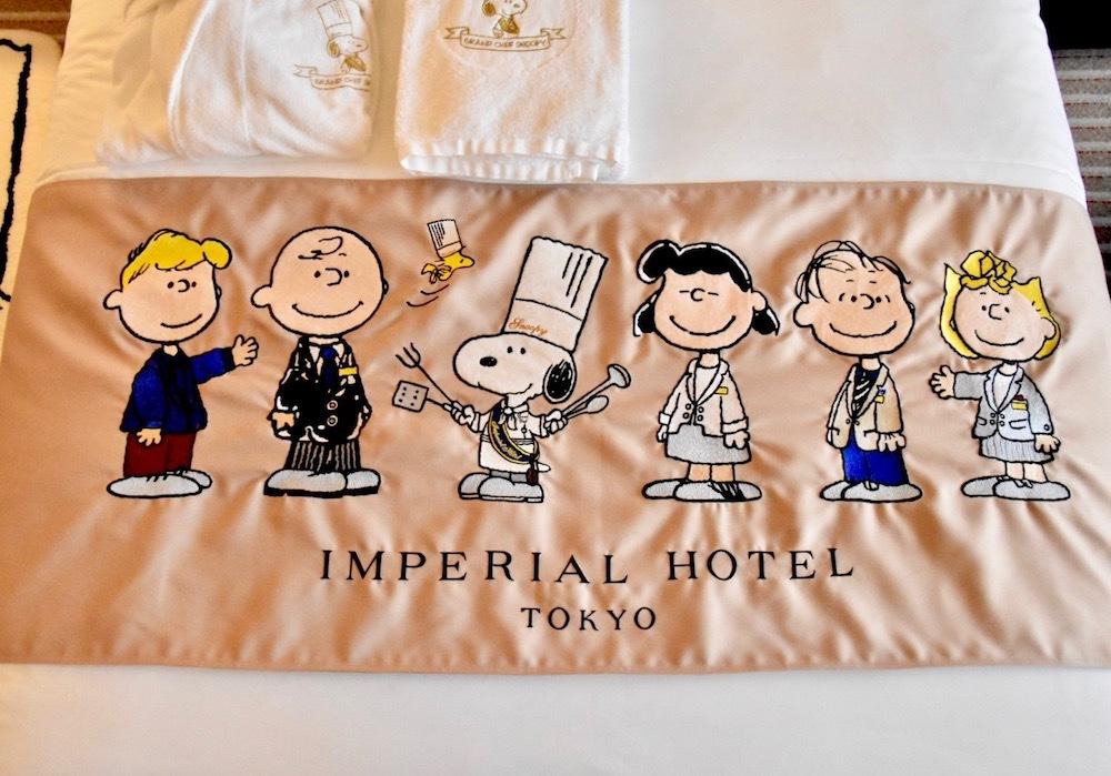 """帝国ホテルの制服姿の""""ピーナッツの仲間たち""""があしらわれたベッドスローは、デザイナー・芦田多恵氏が手がけた。"""