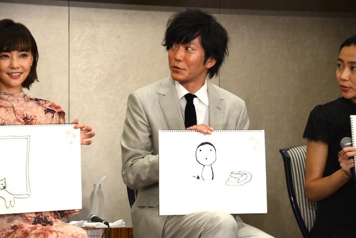 自分で描いた絵を持つ田辺誠一(中央)