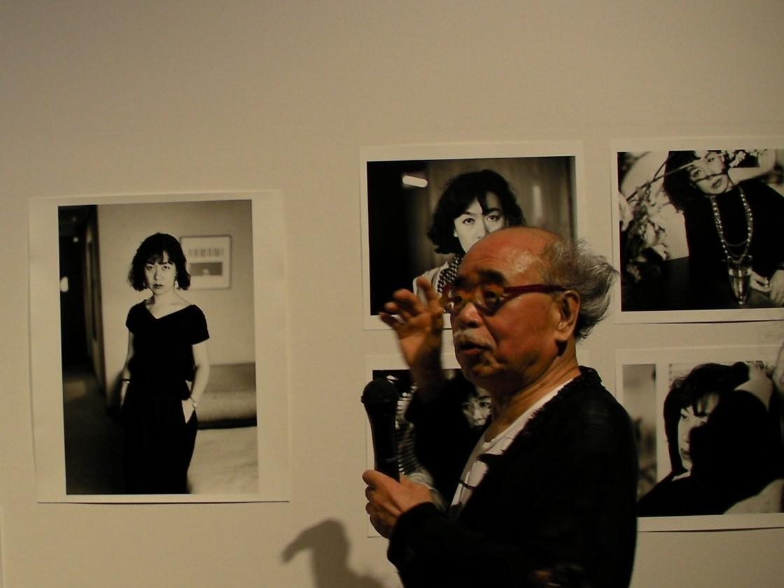 妻・陽子の写真を背景に。左側のポートレイトは遺影に使われた。