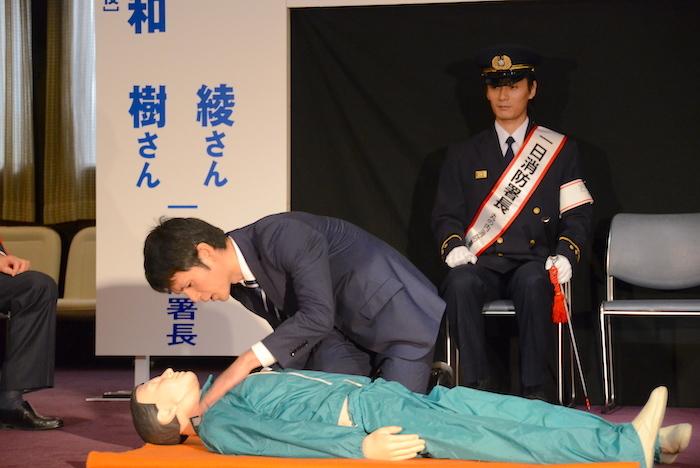 AEDの使い方のデモンストレーションの様子を眺める加藤和樹(右奥)