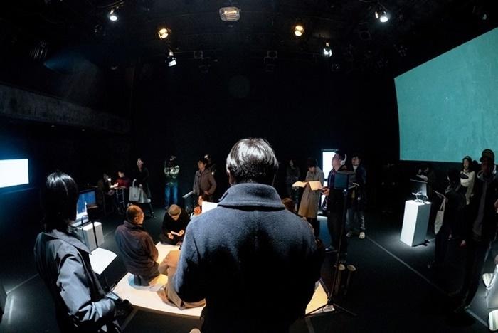 あごうさとし 無人劇『純粋言語を巡る物語-バベルの塔2』(2015年)。観客は会場を自由に歩き回り、映像や音声などを通して役者の存在を感じ取るという試み。