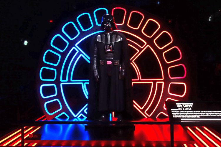 ダース・ベイダー。なお、ジェダイのライトセーバー(光線剣)の色は青か緑、シス(皇帝をはじめとする、負の感情から力を引き出す者のことで、ジェダイと相対する存在)のライトセーバーの色は赤である。