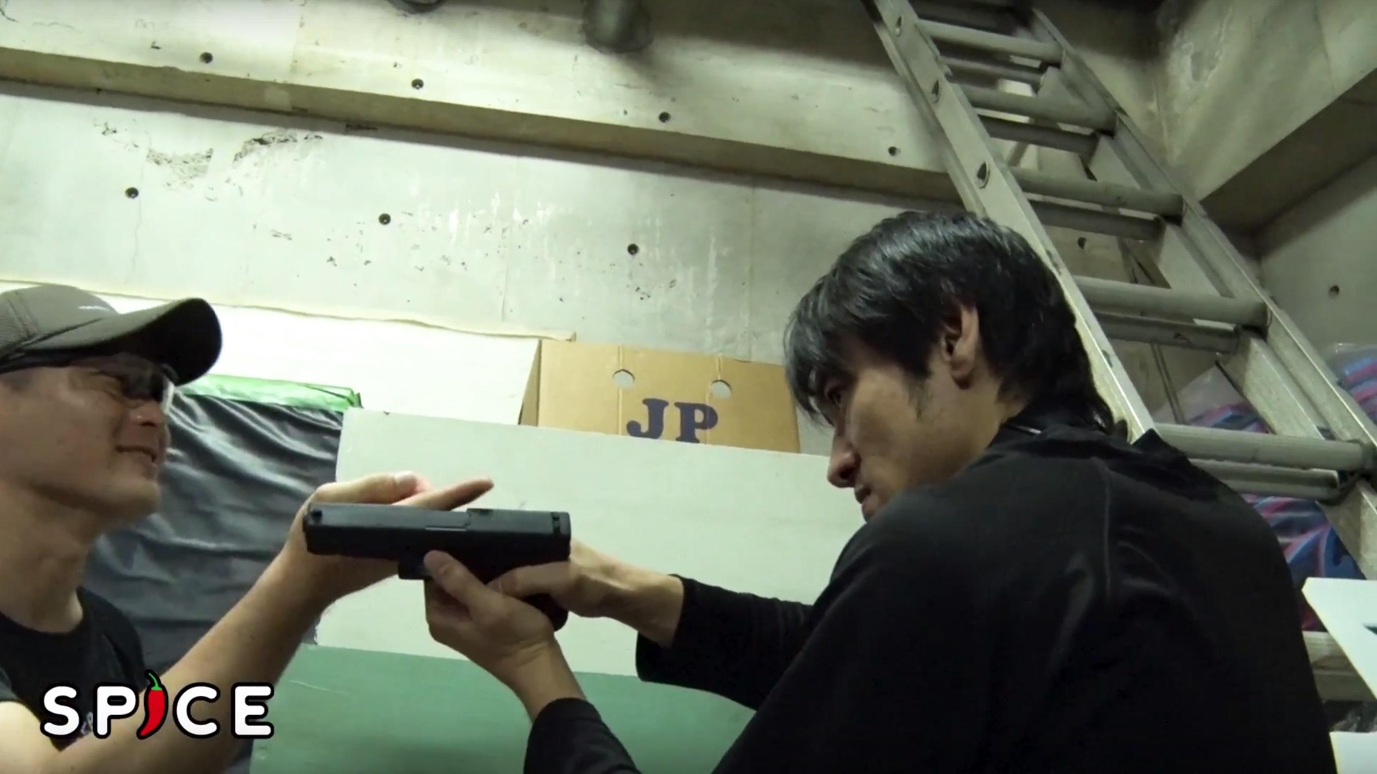 銃の挙動について専門家のレクチャーを受ける俳優・三元雅芸