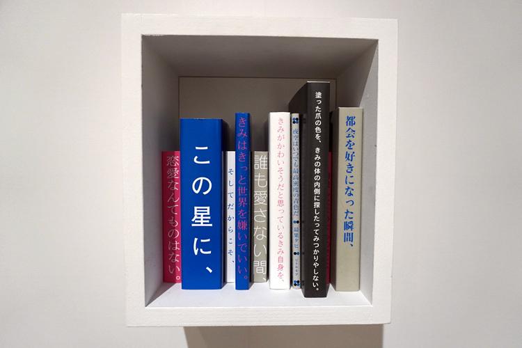 《詩ょ棚》。映画化された詩集『夜空はいつでも最高密度の空色だ』中の一篇「青色の詩」が本棚になっている。