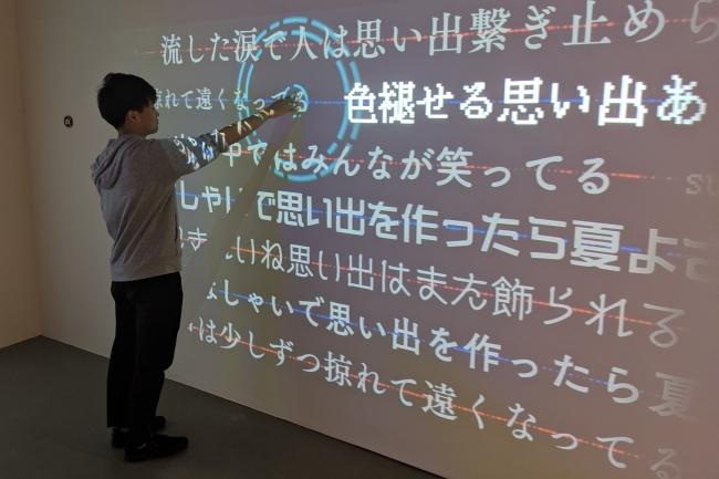 壁に投影された単語をタッチすると、その単語が含まれるフレーズが投影され曲が流れる