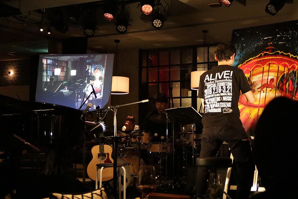 ステージ左側に設置されたスクリーンに、直前に行われたライブ映像が投影される