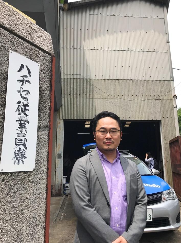 あごうさとし。現在新劇場の開設を進めている倉庫の前にて。 [撮影]吉永美和子