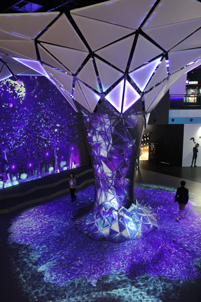入口付近にある巨大な木のオブジェ。写真では紫だが、季節や時間によって変化するという。