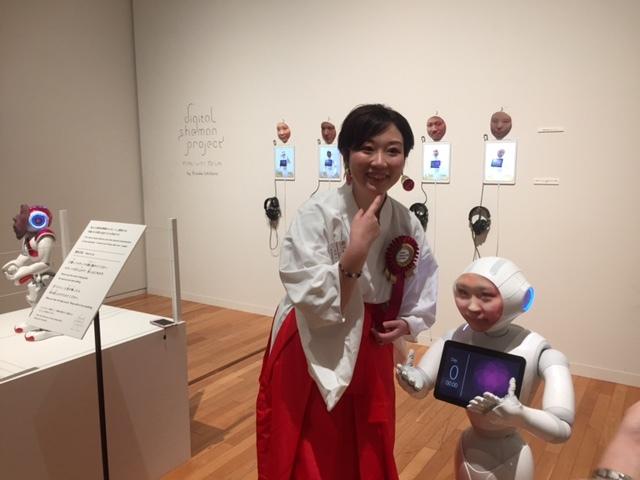 市原えつこ氏と彼女の顔を3Dで映し出した、ロボットのPepper