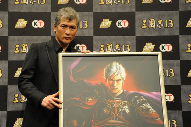 吉川晃司と、彼を武将化した「三國志13」オリジナルキャラクターのパネル。