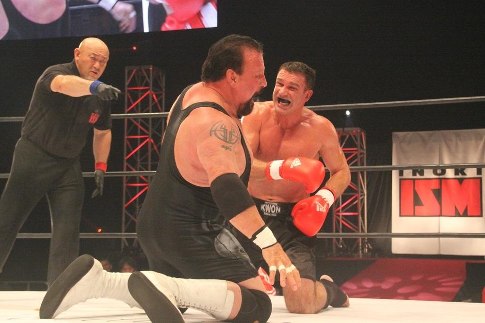 アーツとノートンが膝をついて激しく殴り合い