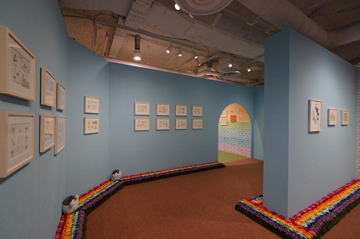 青空をイメージしたブルーの展示室、足元には七色の花が咲く