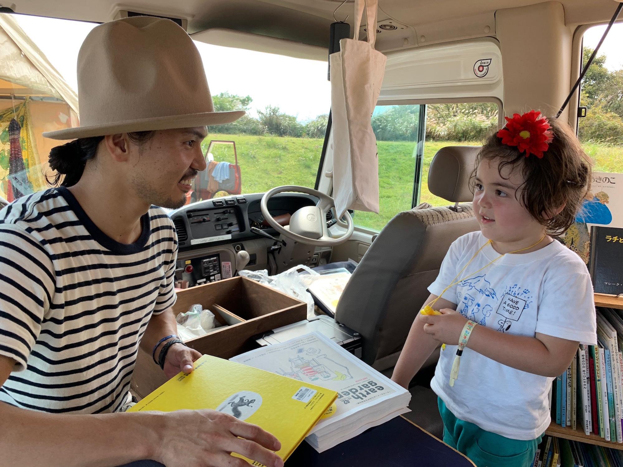 BOOK BUSのお兄さんと絵本について語る3歳児。 撮影=早乙女ゆうこ