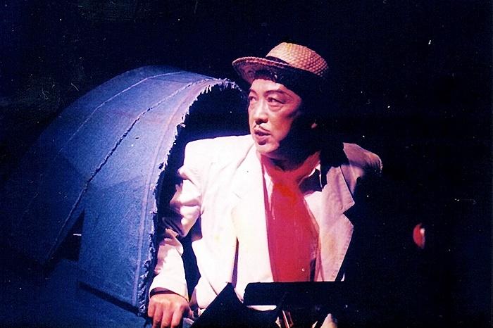 唐組『ジャガーの眼』迷探偵田口を演じる唐十郎。バックに映っているのが、巨大なサンダルでできた探偵オフィス。 ©唐組