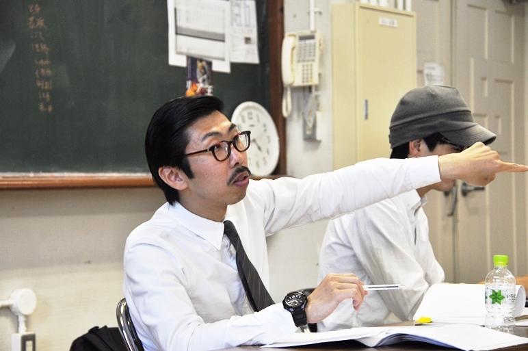 """演出中の村角太洋a.k.a.ボブ・マーサム。稽古中でもネクタイを締めているのがさすが""""紳士""""の劇団だ。 [撮影]吉永美和子"""