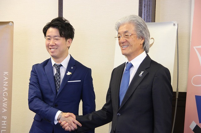 神奈川フィルハーモニー管弦楽団の常任指揮者・川瀬賢太郎(左)と握手を交わす理事長の上野孝