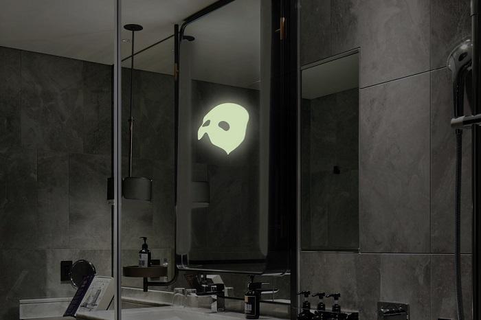暗闇の中鏡に浮かび上がる怪人の仮面